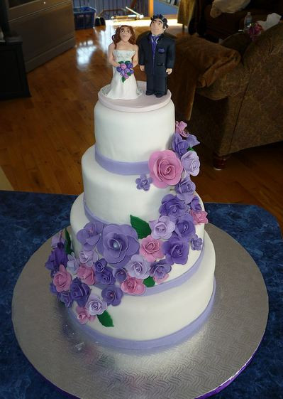 Pink And Purple Wedding Cakes  Four tier round white wedding cake with cascading purple