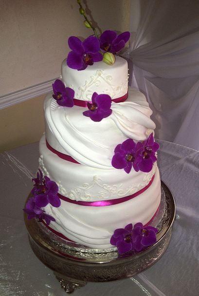 Purple And White Wedding Cake  Four tier white wedding cake with purple flower petals and
