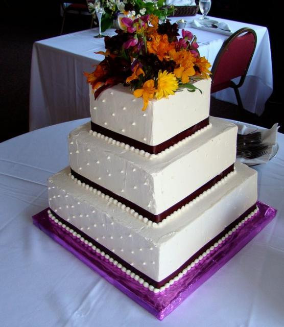 Square Tiered Wedding Cakes  Three tier square white wedding cake with fresh flowers on