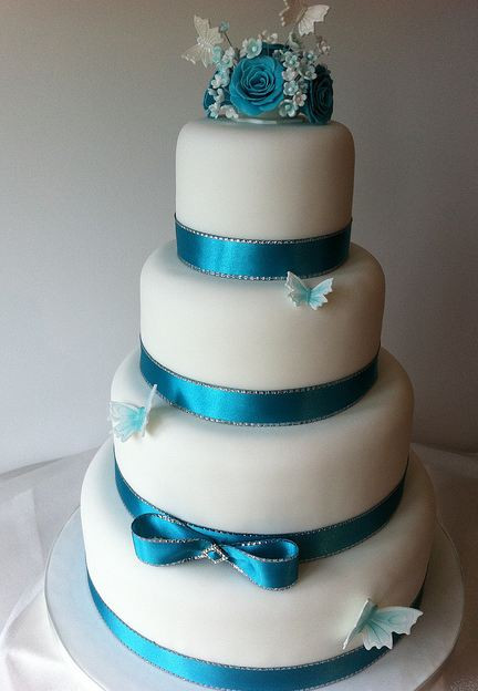 Wedding Cake Blue And White  Four tier round white wedding cake with blue ribbons and