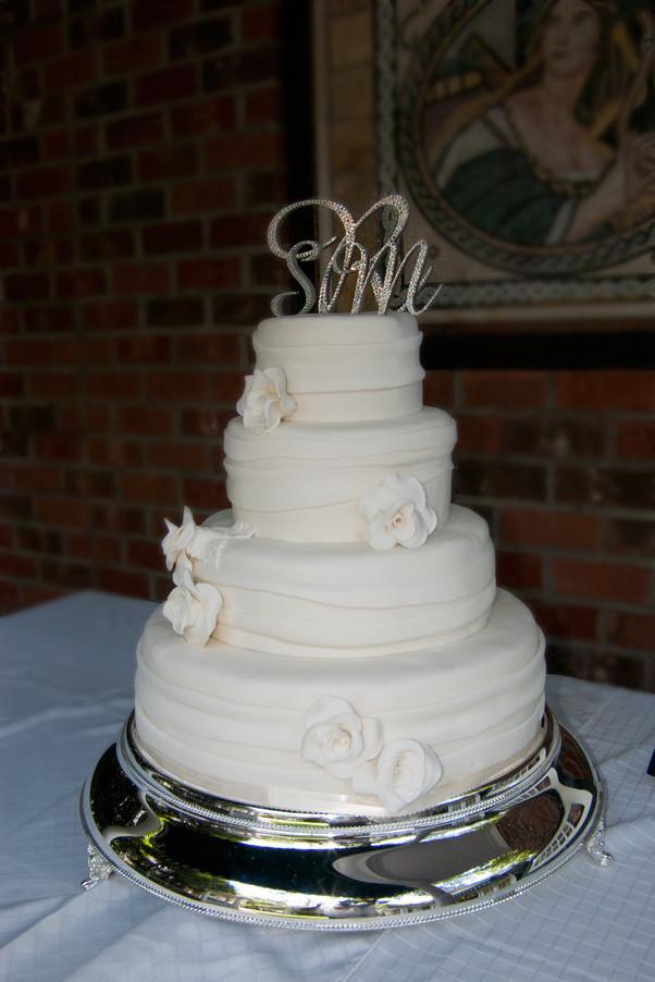 Wedding Cakes Asheville  fondant ribbon wedding cake with white sugar roses • View
